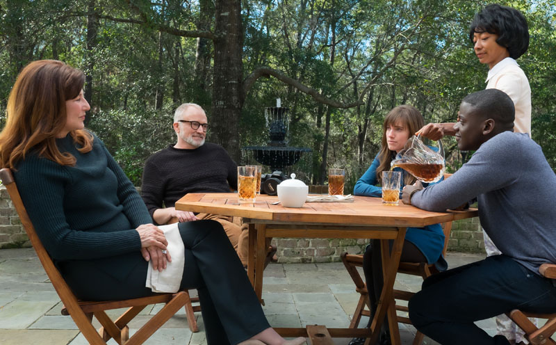 """(L to R) Missy (CATHERINE KEENER), Dean (BRADLEY WHITFORD), Rose (ALLISON WILLIAMS), Georgina (BETTY GABRIEL) and Chris (DANIEL KALUUYA) in Universal Pictures' """"Get Out,"""" a speculative thriller from Blumhouse (producers of """"The Visit,"""" """"Insidious"""" series and """"The Gift"""") and the mind of Jordan Peele. When a young African-American man visits his white girlfriend's family estate, he becomes ensnared in a more sinister real reason for the invitation."""