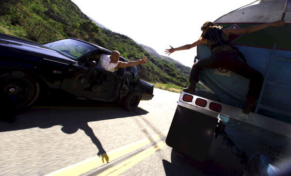 (L to R) Dominic Toretto (VIN DIESEL) reaches for Letty (MICHELLE RODRIGUEZ) during a car chase in the high-octane action-thriller ?Fast & Furious?.