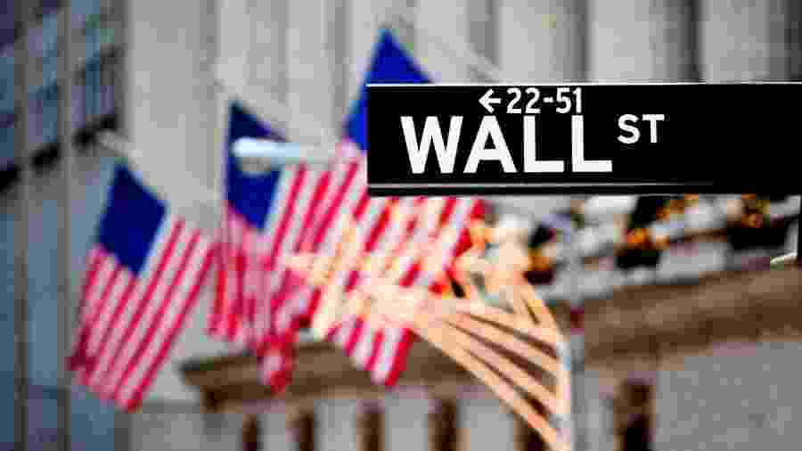 Sign of Wall Street with flags in the background -