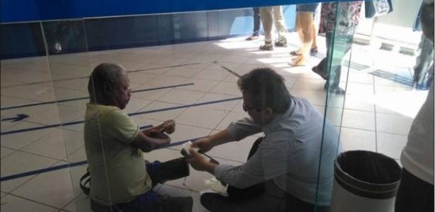 Imagem do gerente Luís Cláudio sentado no chão para atender deficiente físico viralizou