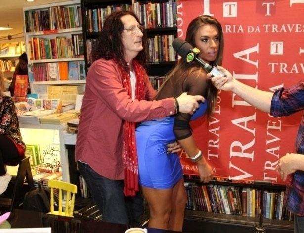 10.abr.2013 - Diretor teatral Gerald Thomas tenta levantar vestido de Nicole Bahls durante lançamento de novo livro e a deixa constrangida. Nicole, que já foi panicat, retornou ao
