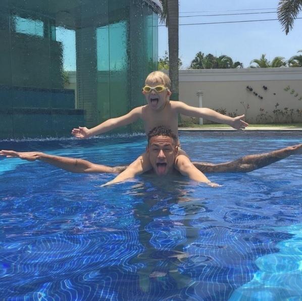 23.dez.2015 - Neymar está aproveitando muito bem suas férias. Nesta quarta-feira, o jogador resolveu curtir uma piscina ao lado do filho, Davi Lucca, em sua mansão no Guarujá, litoral de São Paulo. Na imagem, pai e filho aparecem fazendo caretas