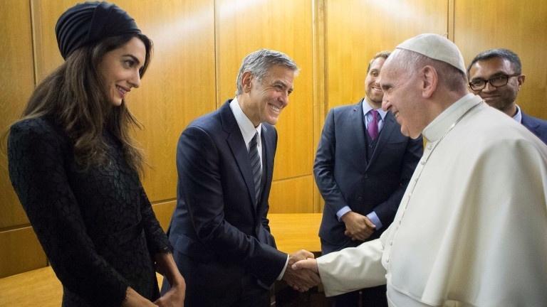 29.mai.2016 - Papa Francisco cumprimenta George Clooney e a esposa, Amal Clooney, durante evento no Vaticano para motivar o trabalho da Scholas Ocurrentes, organização promovida pelo pontífice. Os atores norte-americanos Richard Gere e George Clooney e a atriz mexicana Salma Hayek receberam medalhas do papa por terem aceitado ser embaixadores de um dos projetos artísticos da organização