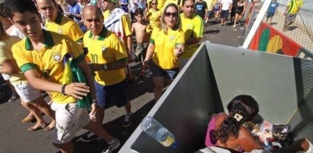 Imagem mostra mulher dentro de lixo sendo ignorada por torcedores a caminho de Brasil x México