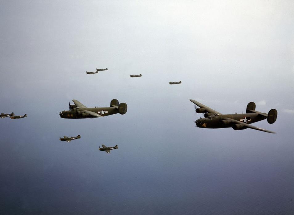 1944 - Par de Consolidated B-24D Liberators é escoltado por um grupo de Curtiss P-40 Warhawks próximos às ilhas Aleutian, no Alaska