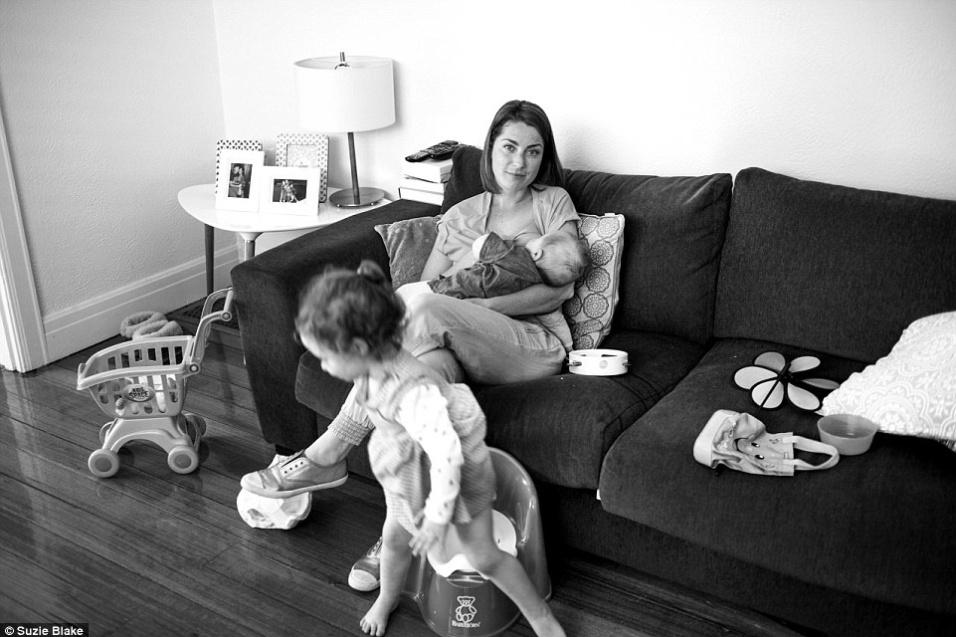 17.nov.2015 - Mãe amamenta bebê enquanto outra filha brinca na sala