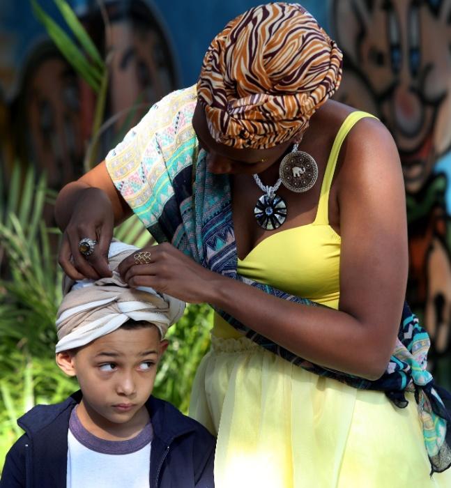 Garotinho aguarda, atento, enquanto integrante do projeto Adeola coloca o turbante