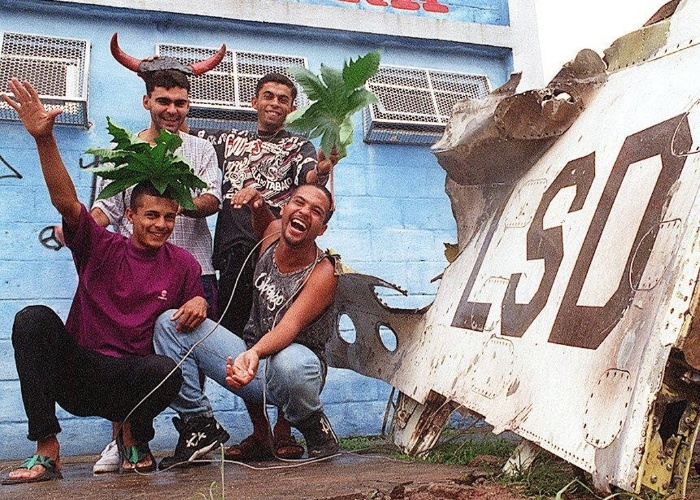 15.mar.1996 - Fãs dos Mamonas Assassinas posam ao lado da asa do avião, retirada do local do acidente que vitimou a banda