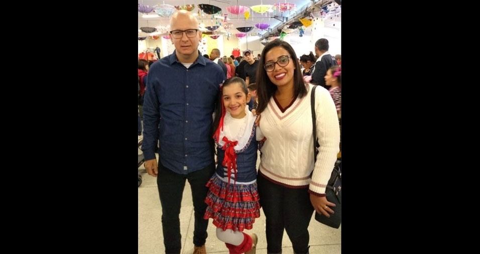 Manuela, de dez anos, com os padrinhos Rodrigo e Tamara no arraial da escola, em São José (SC)