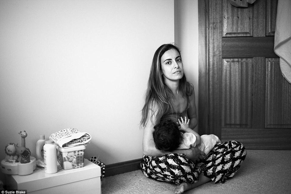 17.nov.2015 - Sentada no chão, mãe mostra a rotina para amamentar filho