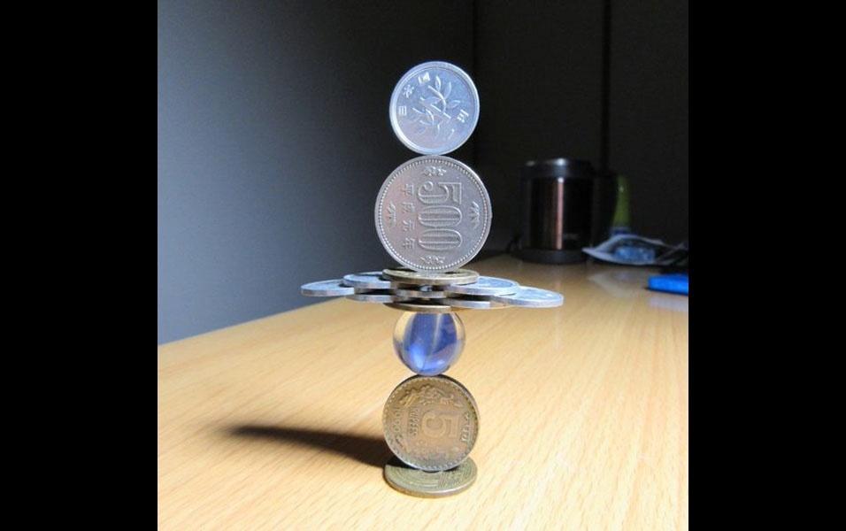 6. Haja concentração e paciência para conseguir empilhar 11 moedas sobre uma bolinha