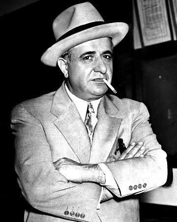 """Nascido Umberto Anastasio, em Tropea, na Calábria, o mafioso Albert Anastasia foi um dos atiradores mais temidos da Murder Inc., a organização criminosa especializada em assassinatos em troca de recompensas, nos Estados Unidos. Após Lucky Luciano estabelecer o poder da Cosa Nostra siciliana em Nova York, com as chamadas """"cinco famílias"""", Albert se tornou o líder da família Gambino, e passou a ser ainda mais temido por sua crueldade. O mafioso foi assassinado em uma barbearia, em 1957, e seus executores nunca foram descobertos"""