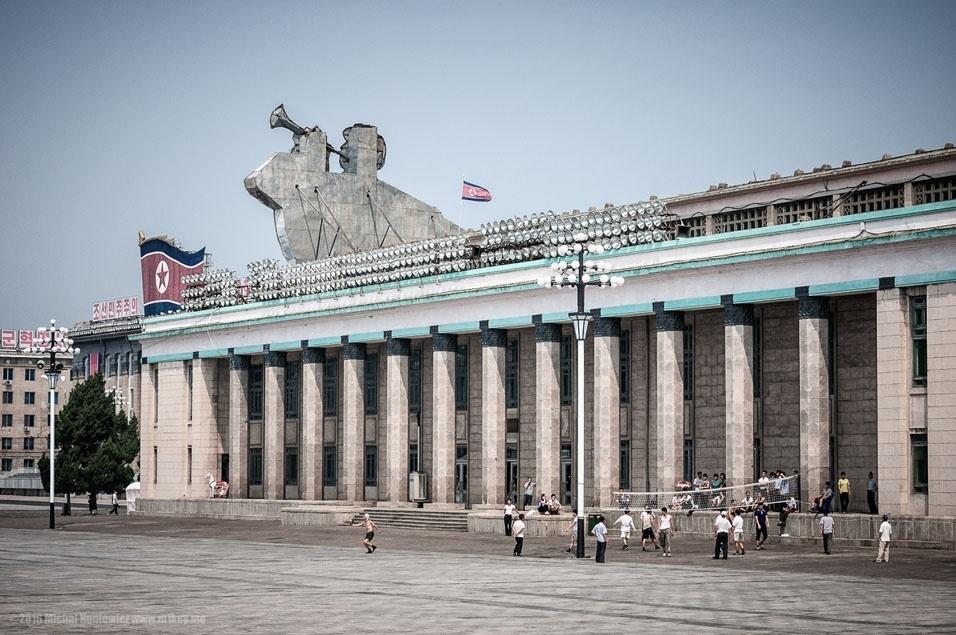 """61. """"O socialismo incentiva atividades esportivas, especialmente as da equipe, para construir um senso de comunidade. Aqui, um grupo de pessoas jogando vôlei na Praça Kim Il-sung"""""""