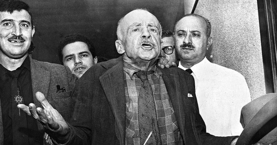 """Italiano radicado no Brasil, Gino Meneghetti era um assaltante que ganhou status de lenda graças aos jornais sensacionalistas da década de 20. Chamado de """"o maior gatuno da América Latina"""", Gino ganhou fama por ser considerado o """"bom ladrão"""" e por suas fugas espetaculares da prisão e dos cercos policiais. Carismático, sempre que era preso, o criminoso dizia que era inocente. Até a sua morte, em maio de 1976, aos 97 anos, também jurava que jamais havia matado um policial ou inocente. Na imagem acima, Gino aparece em foto de 1º de janeiro de 1954"""