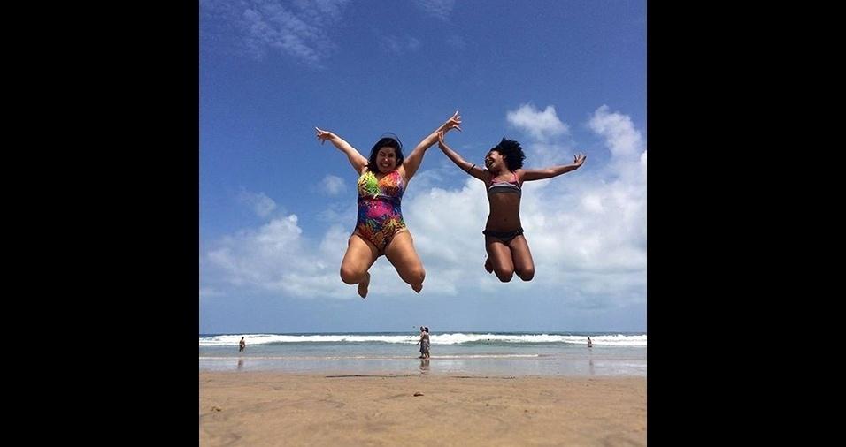 11.jan.2017 - Ao lado de amiga, ela dá um pulo gigante para mais  um clique na areia da praia