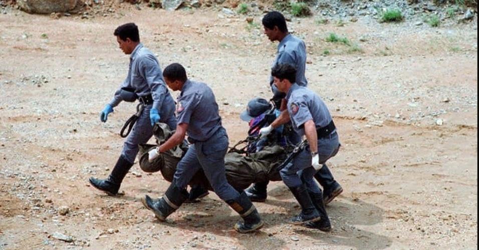 3.mar.1996 - Bombeiros resgatam um dos corpos achados nos destroços do avião em que morreram os cinco integrantes do grupo Mamonas Assassinas