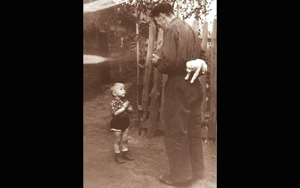 Na imagem acima, um garotinho está prestes a receber um bichinho de estimação de seu avô, em 1955
