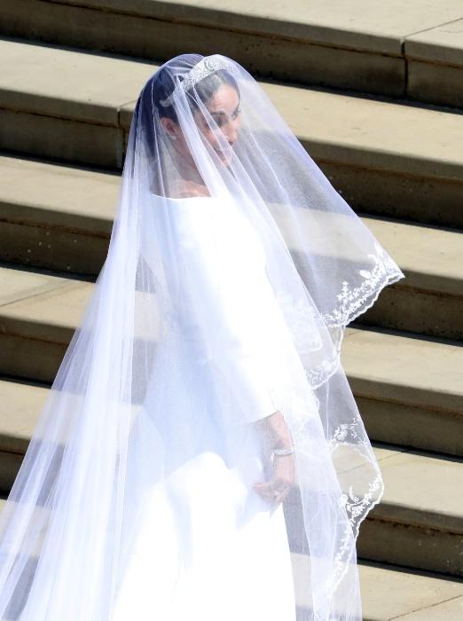 Sorridente, Meghan Markle sobe as escadas da capela do Castelo de Windsor