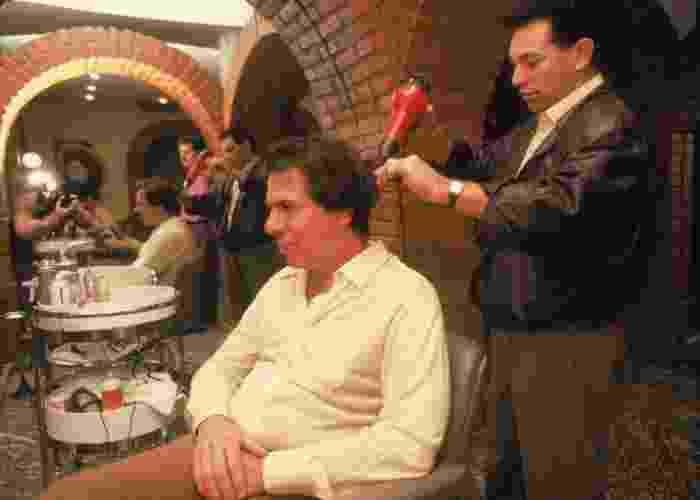 """10.jul.2013 - A revista """"Caras"""" selecionou uma lista com algumas imagens divertidas do apresentador Silvio Santos. Na foto acima, Silvio aparece cortando o cabelo com o cabeleireiro Jassa, no início dos anos 2000 - Reprodução"""
