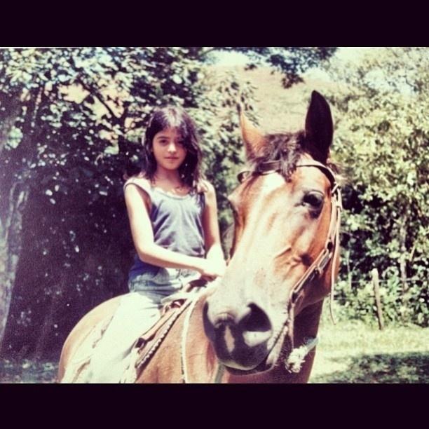 """A atriz Carol Castro compartilhou em sua conta no Instagram uma foto da época em que era criança, montada em um cavalo. """"Infância feliz"""", escreveu a gata na legenda da imagem"""