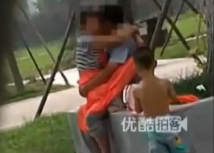 """A cena acima aconteceu em Xi'an, capital da província chinesa de Shaanxi, em uma data indefinida. O flagra mostra um casal que está fazendo sexo em um local público. Eles tentam ser discretos, mas, ao lado deles, está uma criança, que parece um tanto entediada com o movimento. De repente, o menino decide xeretar na relação do casal, chega perto deles, mexe na moça e vai espionar o que está acontecendo por baixo da saia. Sem se importar, o casal continua no """"rala-rala"""". Clique no link para ver o vídeo com o flagra do momento."""