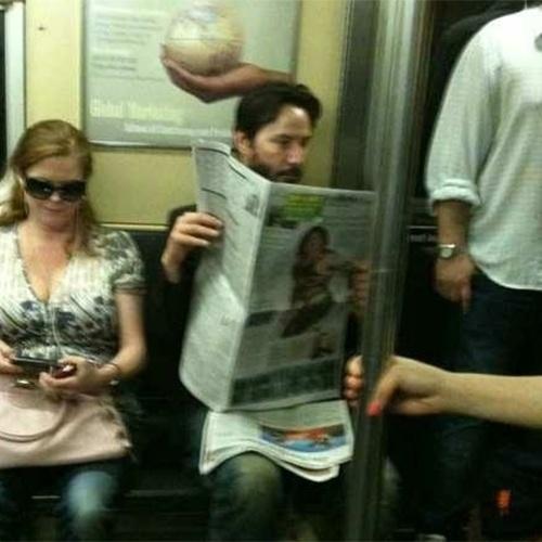 """2010 - Após virar meme com a cena que ficou conhecida como """"Sad Keanu"""" (em que aparece solitário no banco de uma praça), as pessoas começaram a se interessar pelos hábitos pacatos do ator Keanu Reeves e outras fotos de seu cotidiano vieram à tona. Sempre simples e discreto, ele foi flagrado lendo o jornal no metrô"""
