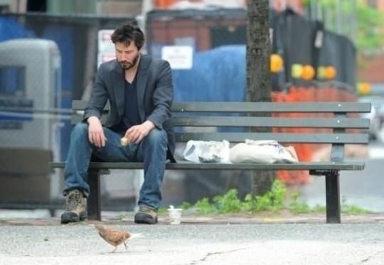 """Mai.2010 - Keanu Reeves virou meme, o """"Sad Keanu"""" (Keanu triste em tradução literal), após protagonizar uma cena inusitada para um badalado ator de Hollywood. Na imagem, ele aparece solitário comendo bolacha no banco de uma praça"""