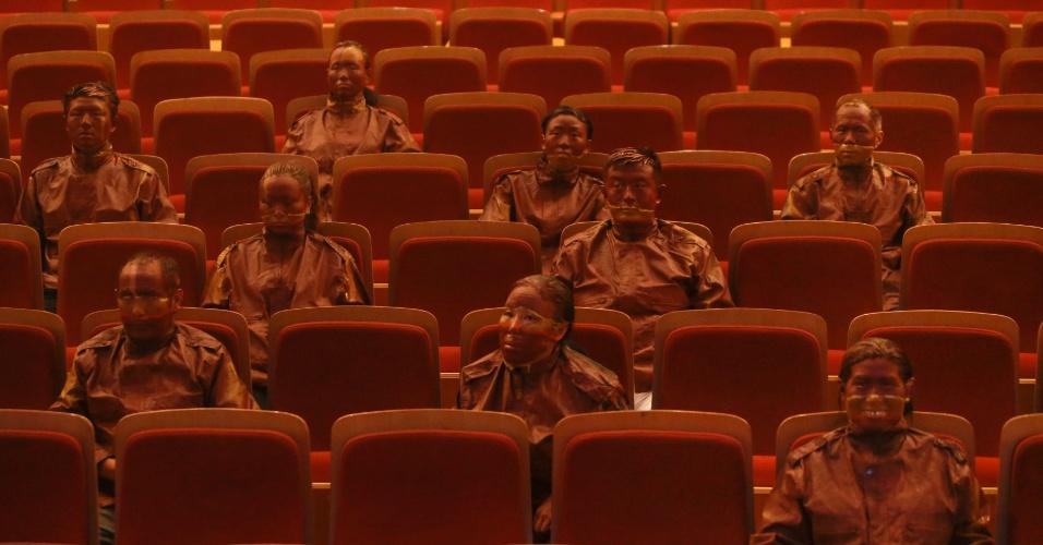 """13.set.2013 - O artista chinês Liu Bolin, conhecido como """"homem invisível"""" por se camuflar no cenário de fotos usando tintas, fez seu truque novamente, """"sumindo"""" com outras 22 pessoas nas poltronas vermelhas de um teatro de Pequim"""