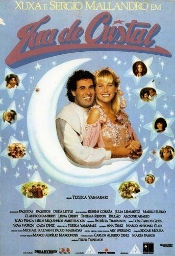 """1990 - Na capa do VHS do filme """"Lua de Cristal"""", em que fez par romântico com a cantora Xuxa; naquele ano, o longa foi a maior bilheteria do cinema nacional, sendo assistido por um total de 5 milhões de pessoas - Mallandro vivia o personagem Bob, e Xuxa, a personagem Maria da Graça"""