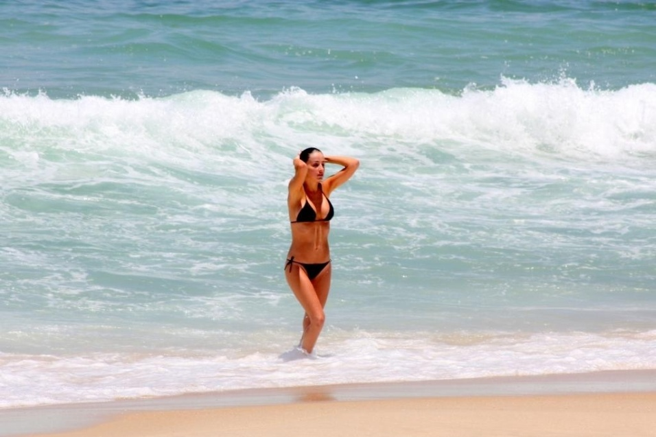 """11.nov.2013 - Erika Mader se refrescou na praia do Leblon, no Rio. Usando um biquíni preto, ela exibiu a sua boa forma enquanto se bronzeava. A jovem, que é sobrinha de Malu Mader, atualmente apresenta o programa """"Brazil Inside Out"""", do canal pago VH1"""