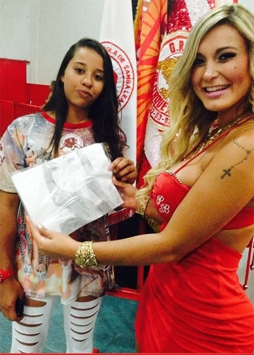 23.nov.2013 - Andressa Urach mostra presente que ganhou de fã durante ensaio da escola de samba paulistana Leandro de Itaquera