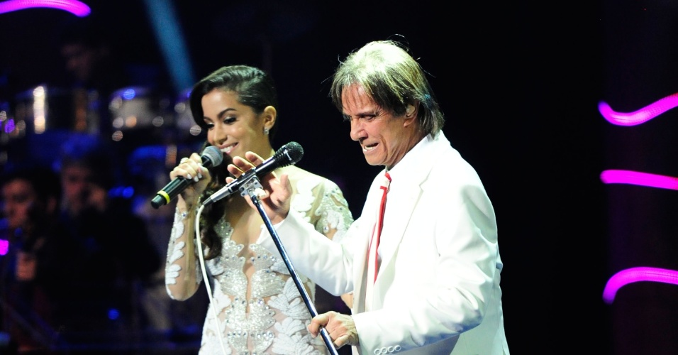 """23.nov.2013 - Em especial de fim de ano da Globo, Roberto Carlos surpreendeu a todos ao cantar uma versão da música """"Show das Poderosas"""" com Anitta. """"Gente, olha só: estou cantando com o Roberto Carlos! Quase desafinei umas cinco vezes. Estou me sentindo poderosa"""", disse a cantora, sendo imediatamente elogiada pelo cantor: """"Mas você é"""". Depois de cantarem juntos, Roberto brincou e disse que ficou """"babando"""", referindo-se ao refrão da música. O cantor também não poupou elogios às bailarinas da funkeira e até brincou quando, a pedido da direção, gravou novamente a música com Anitta. """"Temos que fazer de novo esse número, o que para mim é um prazer muito grande. Muita alegria. Obrigado, Anitta. Obrigado, poderosas"""", disse ele."""