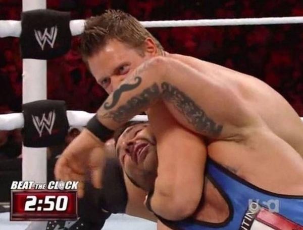E a luta segue com uma chave de braço do bigodão no rapaz de macacão azul! Epa, é apenas a tatuagem no braço do atleta de roupa azulada