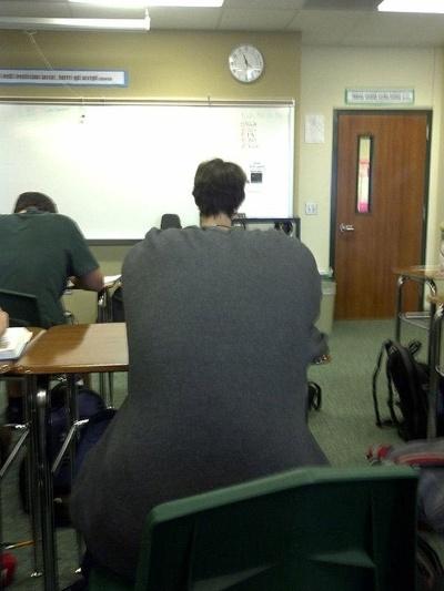 Que costas gigantes e que pequenina cabeça! Ah, não! É apenas um jovem abaixado, sentado logo atrás de outro mais magrinho