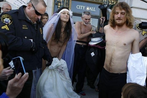 20.dez.2013 - Gypsy Taub e Jaymz Smith se casaram na última quinta-feira (19) em frente à prefeitura de San Francisco, nos Estados Unidos. Logo no começo, eles chegaram ao local vestidos, mas depois a noiva, que é líder do movimento nudista na cidade, optou por um look nada convencional. Ela usou apenas um véu, enquanto o noivo ficou completamente nu. Uma banda acompanhou a cerimônia, que foi realizada por outro ativista pelado. Os recém-casados foram detidos depois do casamento pela polícia da cidade e mantidos dentro de uma van, onde ficaram por algum tempo até serem liberados com uma notificação policial