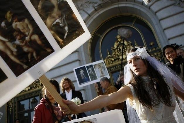 20.dez.2013 - Gypsy Taub e Jaymz Smith se casaram na última quinta-feira (19) em frente à prefeitura de San Francisco, nos Estados Unidos. Logo no começo, eles chegaram ao local vestidos, mas depois a noiva, que é líder do movimento nudista na cidade, optou por um look nada convencional. Ela usou apenas um véu, enquanto o noivo ficou completamente nu. Uma banda acompanhou a cerimônia, que foi realizada por outro ativista pelado. Os recém-casados foram detidos depois do casamento pela polícia da cidade e mantidos dentro de uma van, onde ficaram por algum tempo até serem liberados com uma notificação policial. Na imagem, Gypsy carrega um cartaz com pinturas de nus