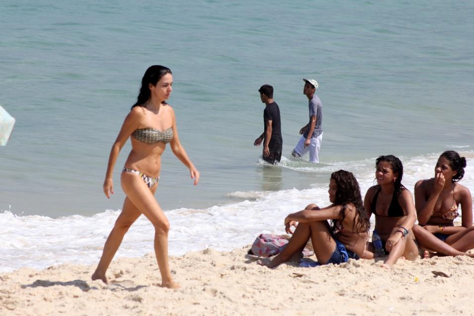 """11.abr.14 - Aos 51 anos, Claudia Ohana mostrou que está em ótima forma ao curtir o dia de sol na praia de Ipanema, no Rio de Janeiro. Atualmente a atriz está no ar na série """"Psi"""", do canal de televisão pago HBO"""