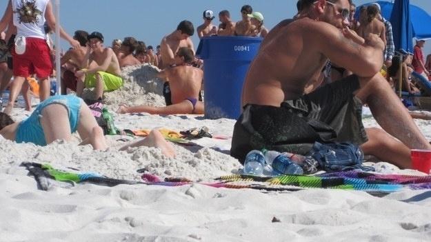 Mas que coisa estranha atrás da caixa azul! Um cara foi à praia para fazer espacate? Claro que não! Ele só sentou à frente de uma garota que estava reforçando o bronze com um  biquíni azul