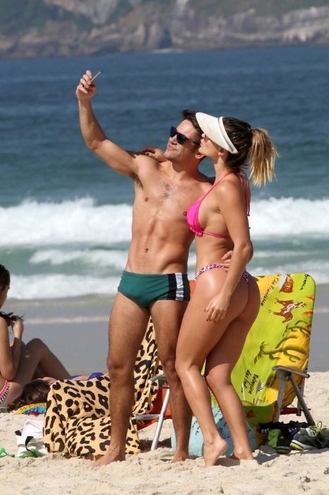 """17.jun.2014 - Laura Keller, conhecida também como a ex-Mulher Múmia, tira fotos com amigo na praia na Barra da Tijuca, no Rio de Janeiro. A beldade atua como a stripper Luiziane em """"Pé na Cova"""""""