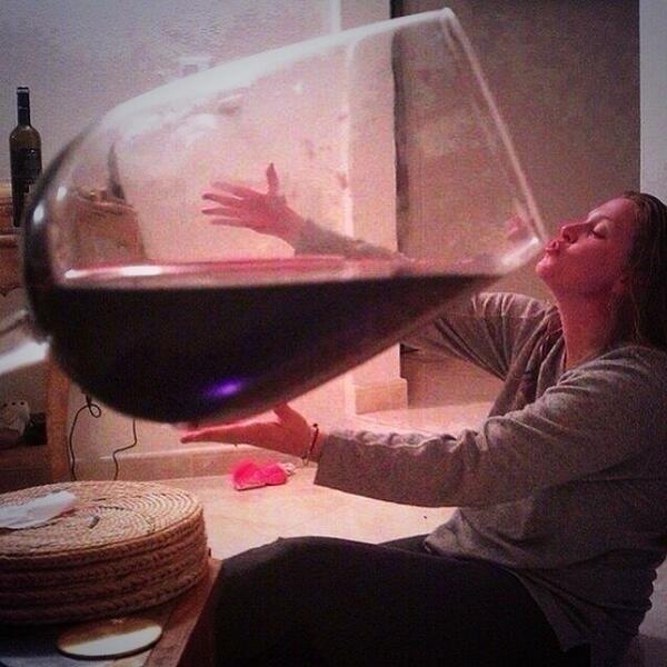 Ao olhar a imagem, parece que a jovem está segundo um enorme copo de vinho. Mas, na verdade, tudo é uma questão de perspectiva de como a foto de uma taça de vinho foi tirada