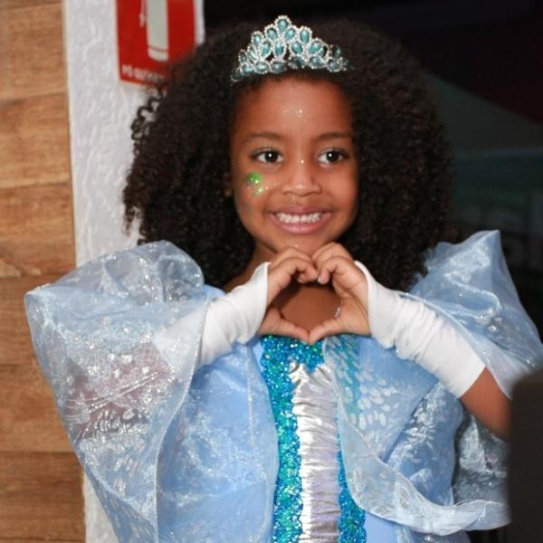 25.ago.2014 - Filha da cantora Negra Li, a pequena Sofia posa para os fotógrafos fazendo um coração com as mãos durante sua festa de 5 anos