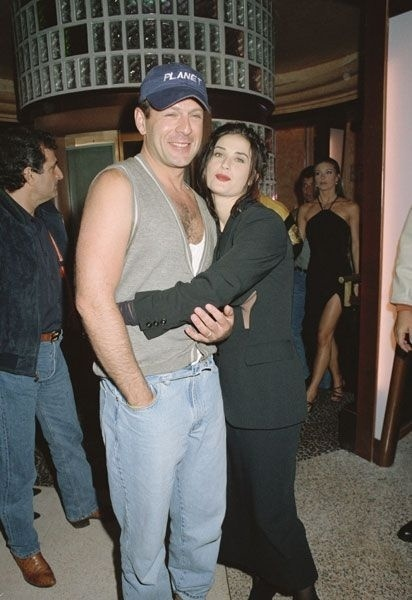 Década de 90: vestindo um distinto colete de lã, o ator Bruce Willis abraça a mulher Demi Moore