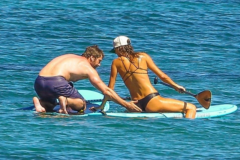 """26.set.2014 - O ator escocês Gerard Butler, 44, curtiu um dia de praia em Malibu, nos Estados Unidos, acompanhado de uma garota misteriosa, que estava de biquíni e não escondeu a boa forma. Ambos aproveitaram o clima para praticar stand up paddle, enquanto trocavam carinhos mais quentes com direito a """"mão boba"""" do ator no bumbum da mulher"""