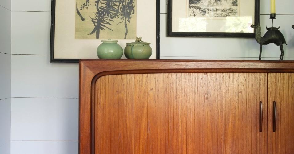 Detalhe de um cantinho da casa, com obras de arte na parede e um móvel antigo decorado com potes de porcelana.