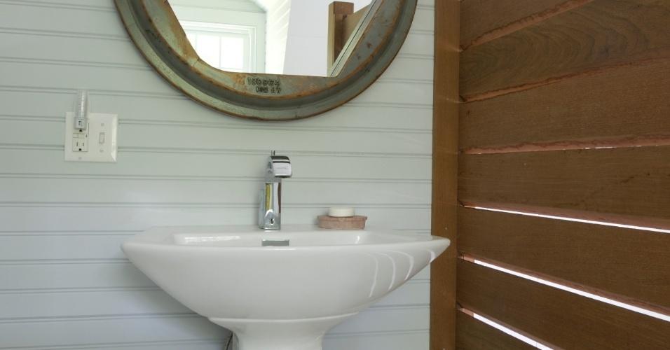 No banheiro dos hóspedes, a porta que dá acesso ao chuveiro é feita de ipê. Destaque ainda para o espelho com moldura