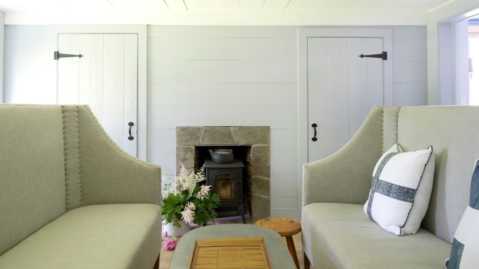No living, os sofás claros com espaldares altos são da Restoration Hardware. Ao fundo, o lugar da lareira é ocupado por um antigo fogão de ferro.