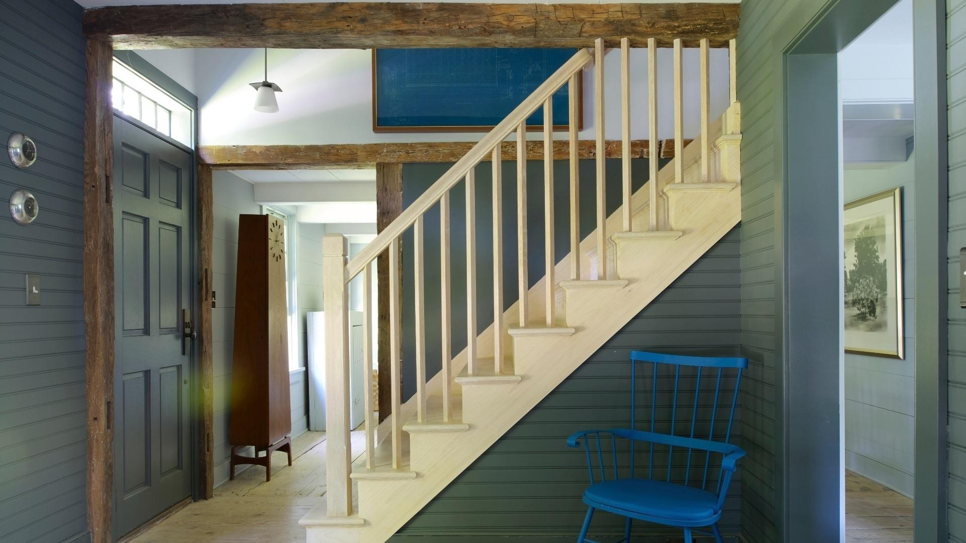 No foyer junto à escada, as paredes de madeirinha ganharam pintura cinzenta. Ali, as vigas robustas foram deixadas à mostra. Destaque ainda para a cadeira antiga, modelo Windsor, pintada de azul.