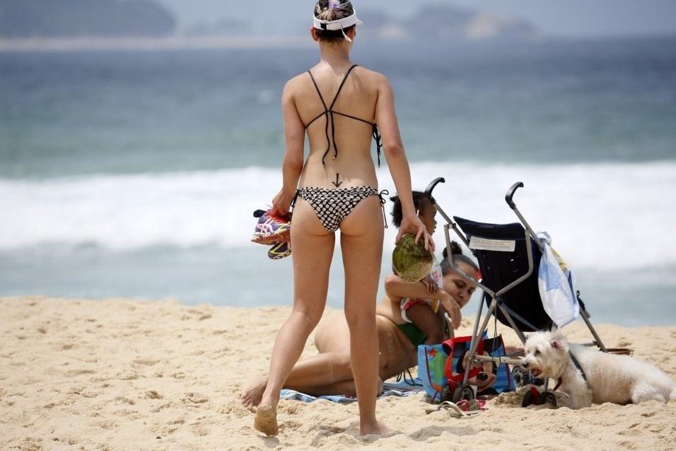 16.out.2014 - A atriz global Bruna Linzmeyer curtiu um dia de praia no Leblon, zona Sul do Rio de Janeiro. Após o mergulho, a beldade deixou uma tatuagem em formato de seta à mostra. O desenho fica acima do bumbum
