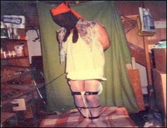 """Entre 1974 e 1991 - Dennis Rader, assassino BTK (Bind-Torture-Kill, que em tradução livre quer dizer """"Amarrar-Torturar-Matar"""") - Na infância, ele maltratava animais, quando cresceu tornou-se um sádico assassino. Vaidoso, Dennis gostava de guardar recordações de suas vítimas, para poder relembrar e reviver os momentos dos assassinatos, remontando as cenas de seus crimes e planejando os próximos. Um de seus passatempos era desenhar as ideias que tinha para matar a próxima pessoa. Outra diversão do serial killer era usar as roupas de suas vítimas e remontar as cenas dos crimes, amarrado e com algo cobrindo sua cabeça, exatamente como fazia com as pessoas que matava. Na foto acima, ele aparece no porão da casa de seus pais com a camisola que roubou de uma das vítimas, Dolores, 62"""