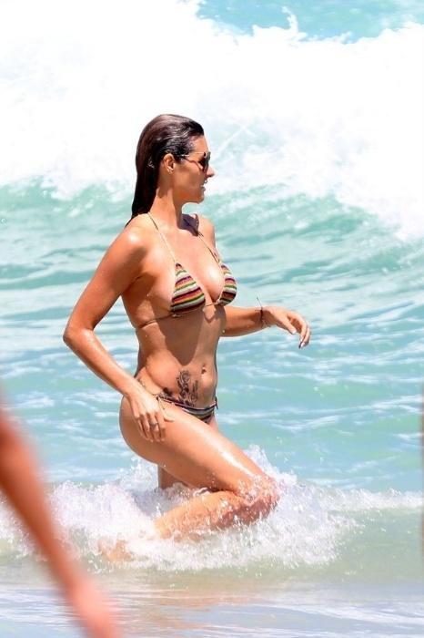 6.dez.2014 - A modelo e apresentadora Fernanda Lima mostrou que está em ótima forma ao curtir o dia de sol na praia do Leblon, no Rio de Janeiro. Ela também deixou à mostra a tatuagem sexy de rosas que possui no abdômen sarado